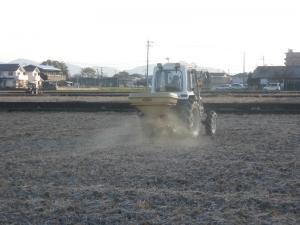 S170124武市さんがテクノペレット散布で左奥では息子さんがすでに耕運中